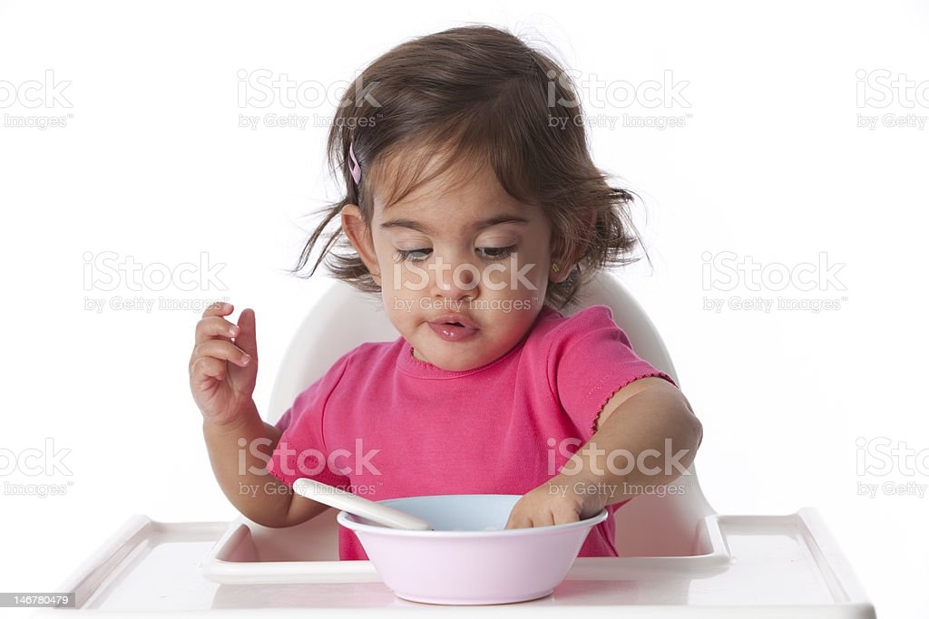Baby girl is eating with her hand royalty-free stock photo
