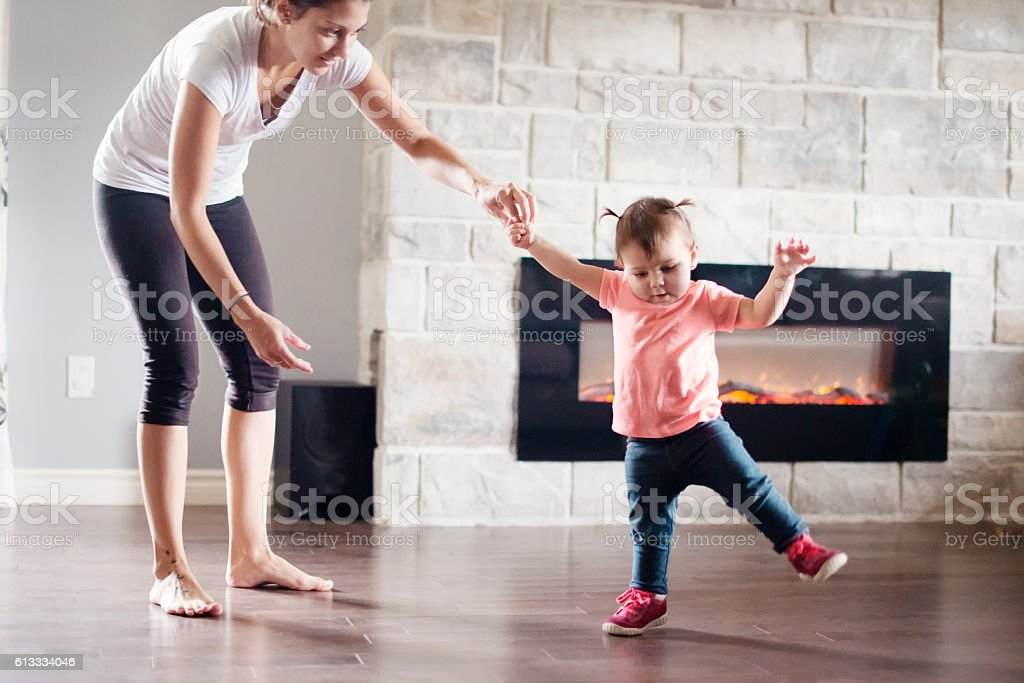 Baby girl is walking her first steps with her mother stock photo