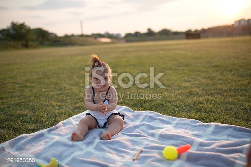 Ten months old baby girl playing with toys in park on blanket on hot summer day