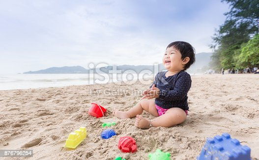 istock Baby girl laughing on the beach. Can use for learning and playing concept. 876796254