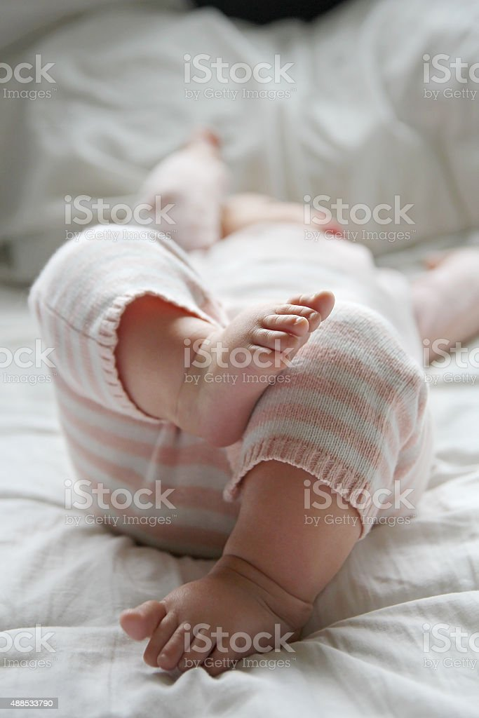 Baby Girl Laying on Bed stock photo