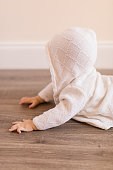 A 7-month old baby girl wearing a white hoodie and jean shorts laying on a wooden floor.