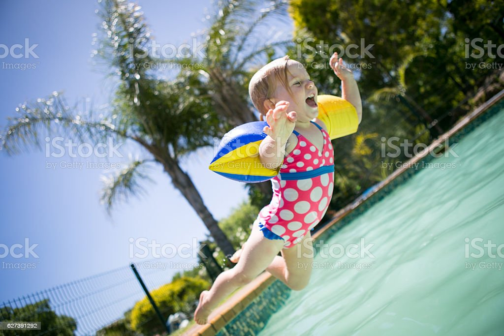 Baby girl leaps into a swimming pool stock photo