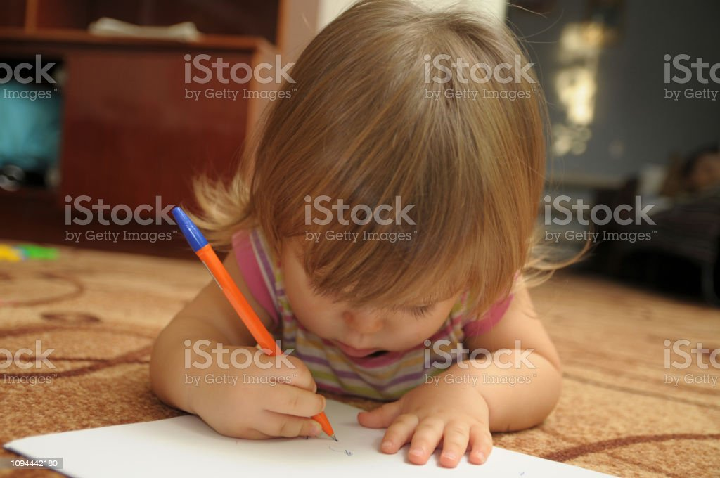 Baby girl learning to write and paint in home environment lying on...