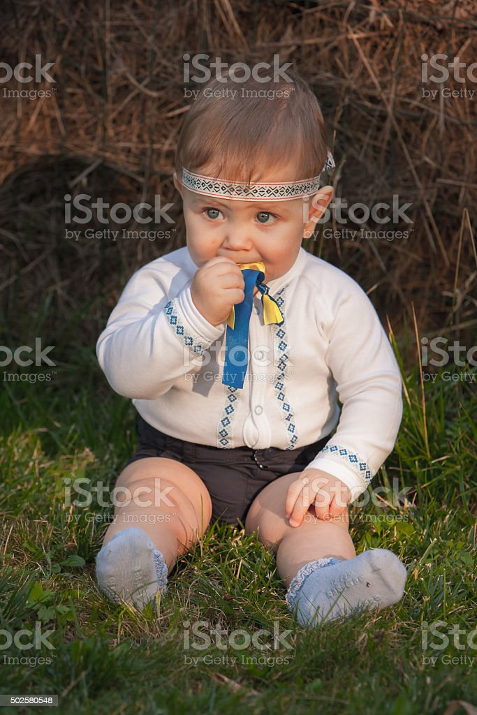 Baby girl, less than a year old on green grass stock photo