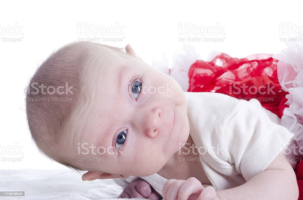 Baby girl lifting head with sweet expression. royalty-free stock photo