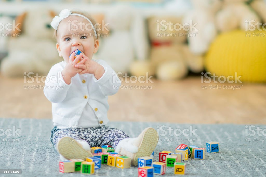 Baby Girl Looking and Playing with Toy Blocks stock photo