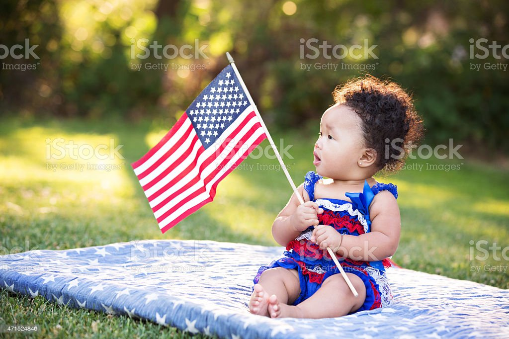 Baby Girl Looking At American Flag stock photo
