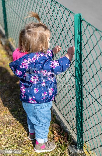 Sweet 17-Months Old Baby Girl Looking Through The Meral Fence. Outdoor And Head Photography