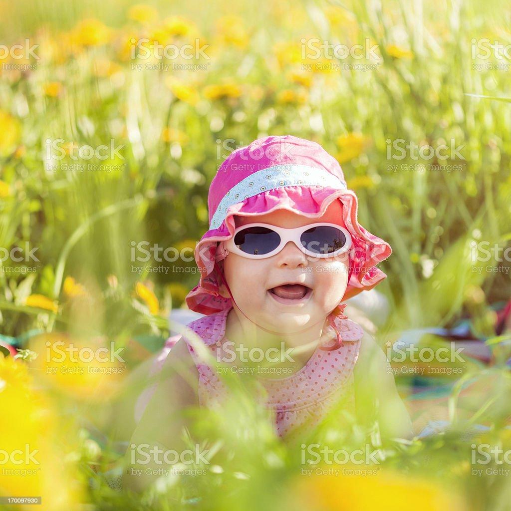 Baby girl lying in a field stock photo