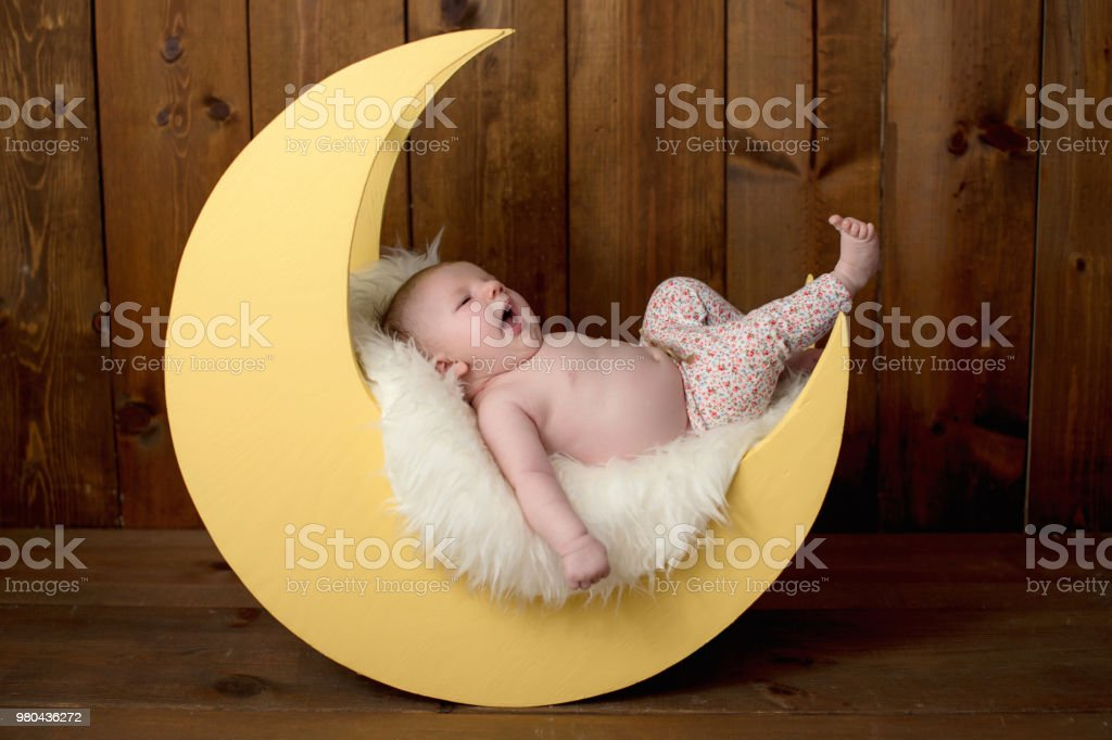 Baby Girl Lying on a Moon Shaped Photo Prop stock photo