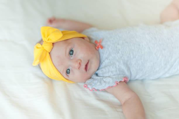 Baby girl lying on bed stock photo