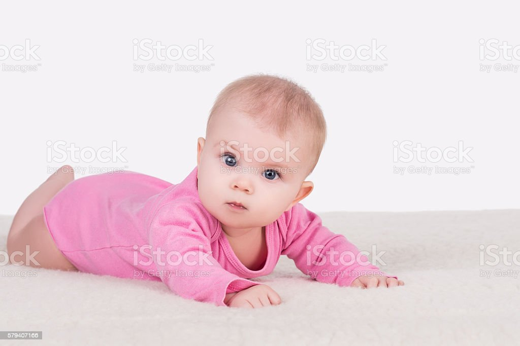 baby girl lying on blanket and try crawling stock photo