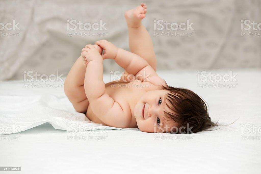 Baby girl lying on blanket indoors stock photo