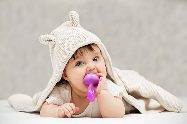 Baby girl lying on blanket indoors