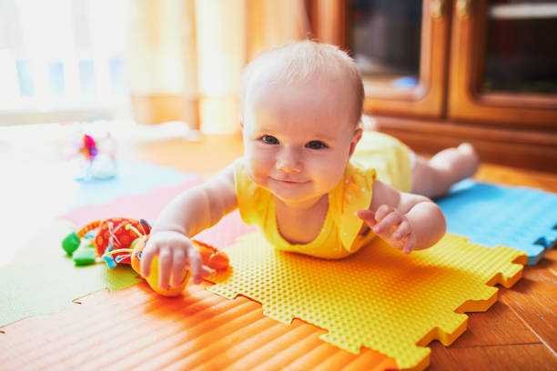 baby girl lying on colorful play mat on the floor stock photo