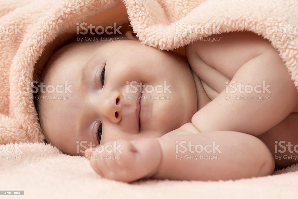 Baby girl lying under a blanket smiling stock photo