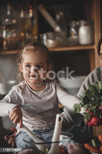 istock Baby girl mixing vegetables, preparing salad 1135709063
