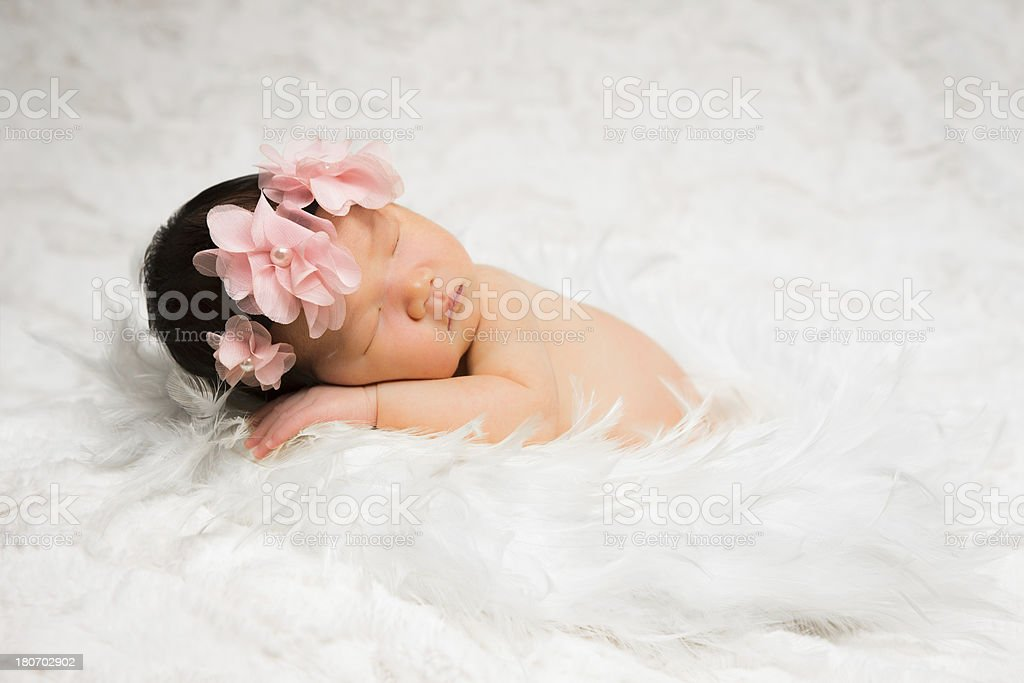 Baby girl newborn laying in feather wreath royalty-free stock photo