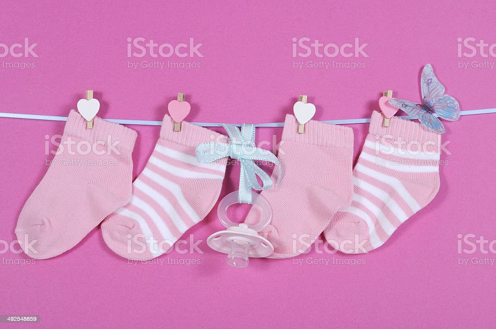 Baby girl nursery socks and dummy pacifier hanging from pegs stock photo