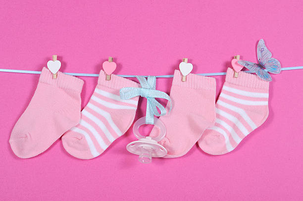 baby girl nursery socks and dummy pacifier hanging from pegs - its a girl stock photos and pictures