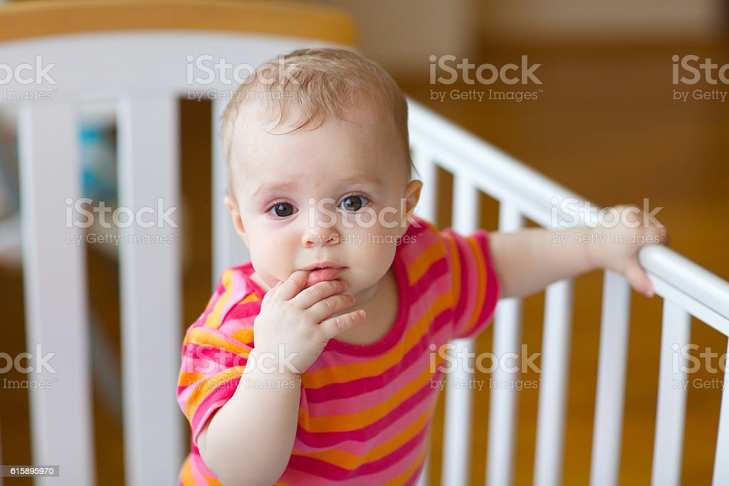 Baby girl of eight months in its bed stock photo
