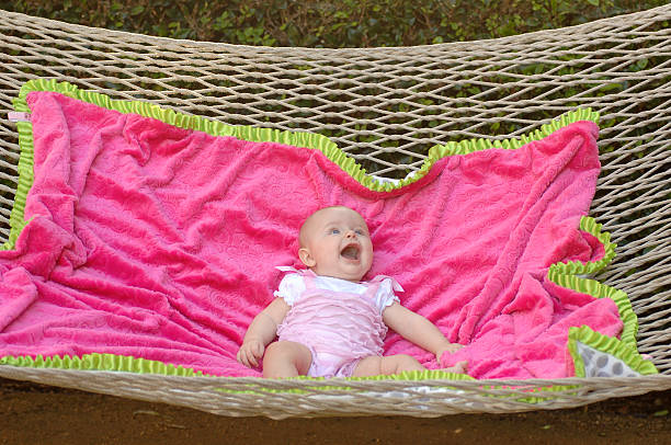 Baby girl on a blanket on a hammock stock photo