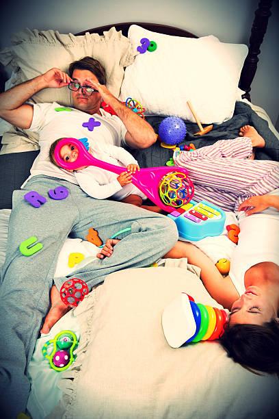 baby mädchen auf dem bett mit ihren eltern unordentlich - marvel schlafzimmer stock-fotos und bilder