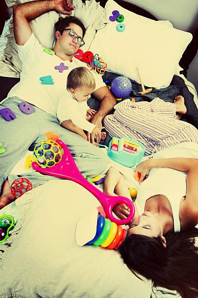 baby mädchen auf dem bett mit ihren eltern unordentlich - fails zum thema eltern stock-fotos und bilder