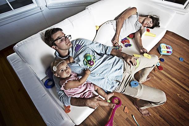 baby mädchen auf einem unordentlich couch mit ihren eltern - fails zum thema eltern stock-fotos und bilder