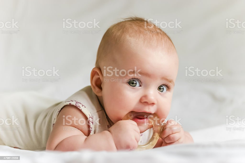 Baby girl on her stomach with teether in the mouth Six-month baby girl on her stomach with teether in the mouth 6-11 Months Stock Photo