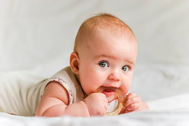 Baby girl on her stomach with teether in the mouth Six-month baby girl on her stomach with teether in the mouth baby girls stock pictures, royalty-free photos & images