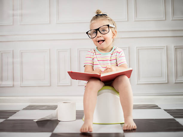 Baby girl on potty with notebook stock photo