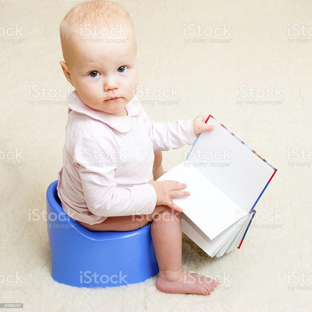 Niña bebé el orinal de niño con libro abierto - foto de stock