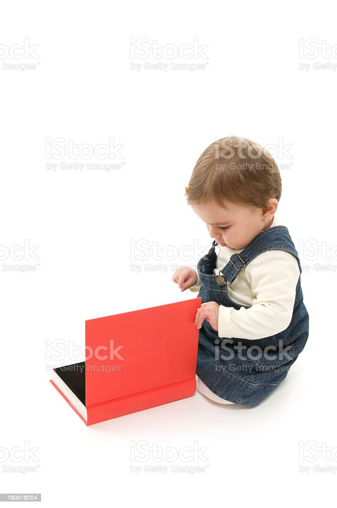 Baby girl opening the red book, isolated on white royalty-free stock photo