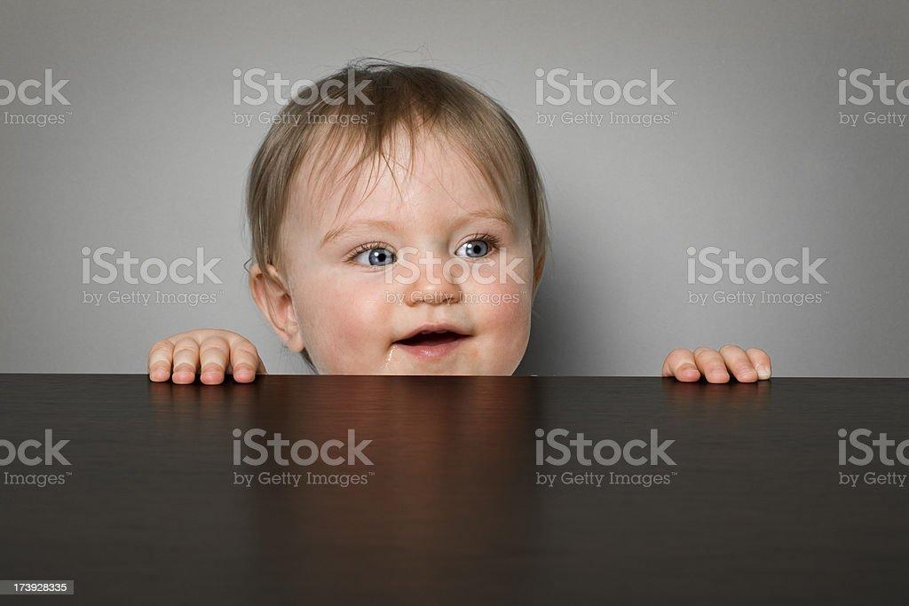 Baby girl peeking over a table royalty-free stock photo