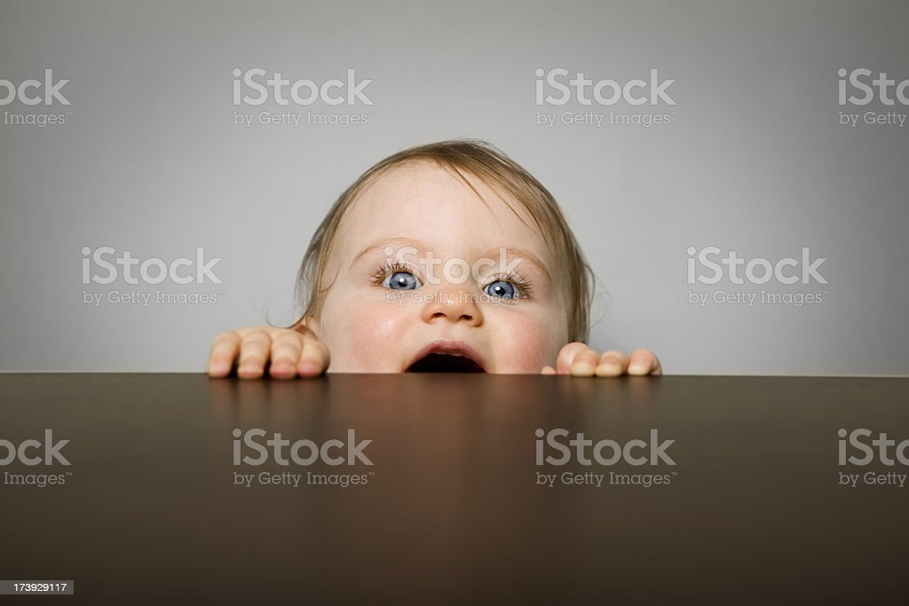 Bébé fille Regarder à la dérobée sur une table - Photo