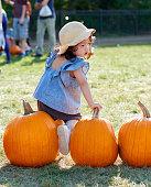 istock Baby girl picks pumpkin in the farm 913835456