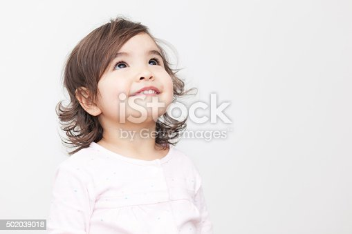 Smiling baby girl looking up on the white background