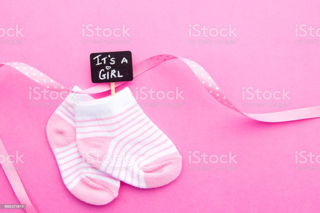 Baby Girl - pink and white socks with ribbon on pink background with It's a Girl blackboard sign stock photo