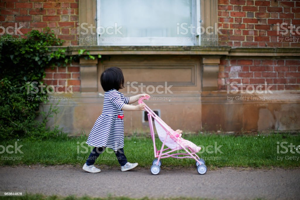 baby girl play baby stroller in spirng garden stock photo