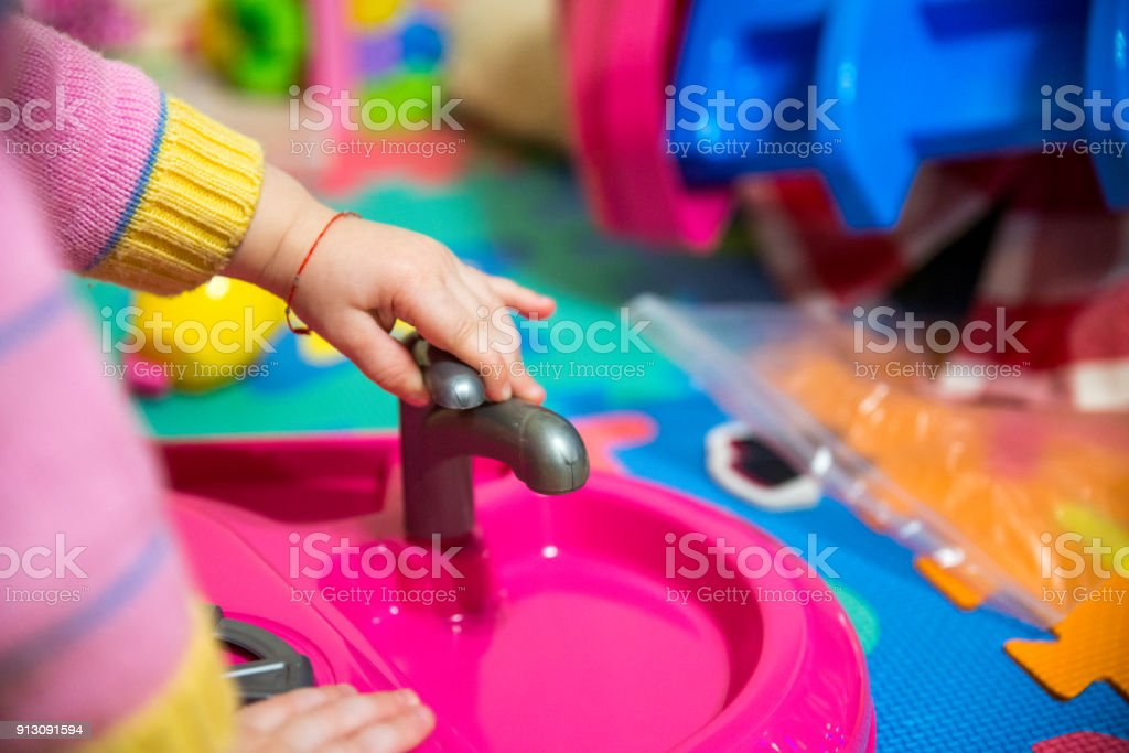 baby girl play with plastic kitchen toys stock photo