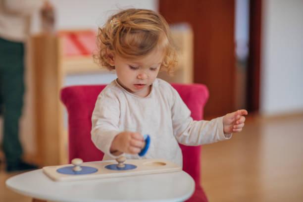 Baby girl playing alone in preschool classroom stock photo