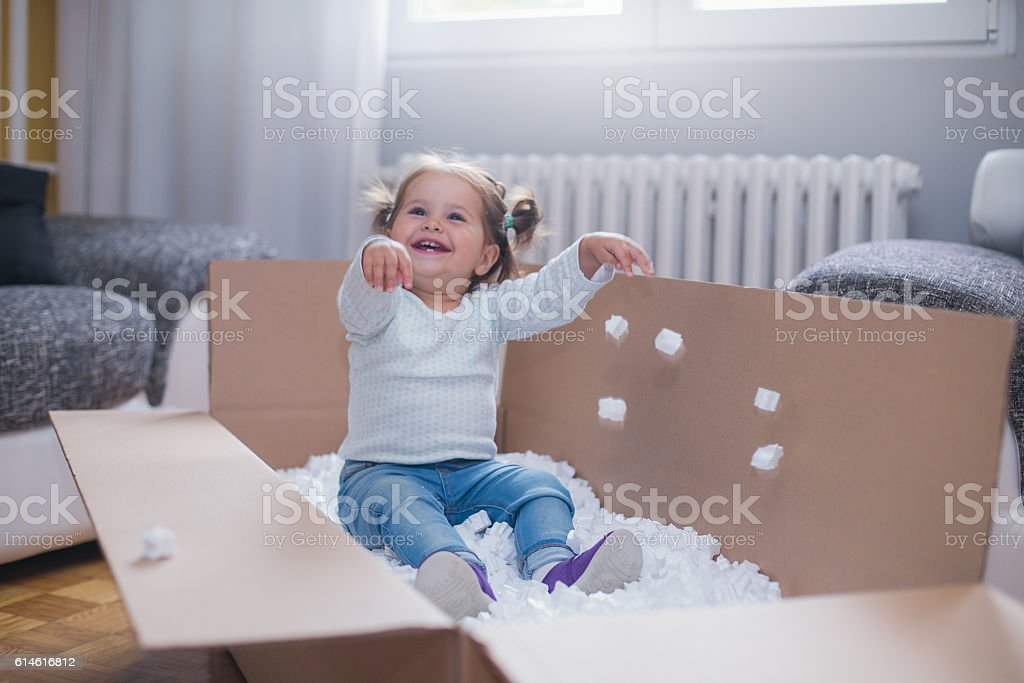 baby girl playing in box with styrofoam pellets stock photo