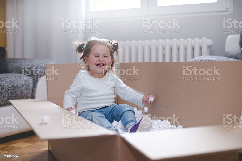 baby girl playing in box with styrofoam pellets​​​ foto