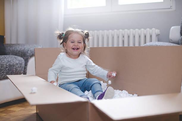 baby girl playing in box with styrofoam pellets - umzug transport stock-fotos und bilder