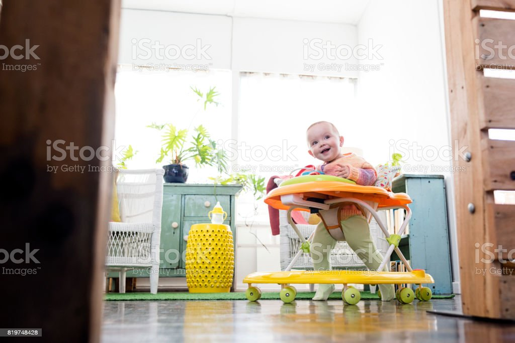 Baby girl playing in walker stock photo