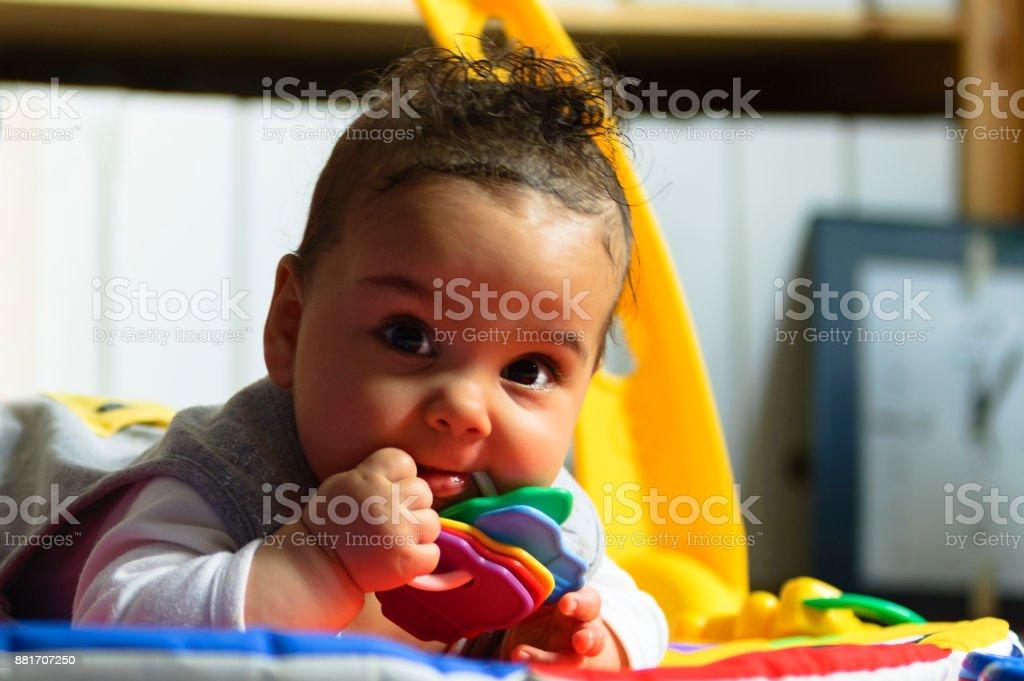 Baby girl playing on floor mat stock photo