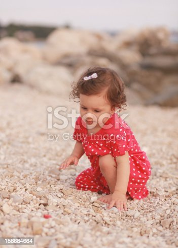 147878016 istock photo baby girl playing on the beach 186684664