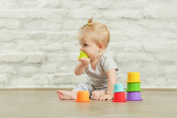 Babymädchen spielen auf dem Boden mit pädagogischen Plastikbecher, Frühförderung Konzept – Foto
